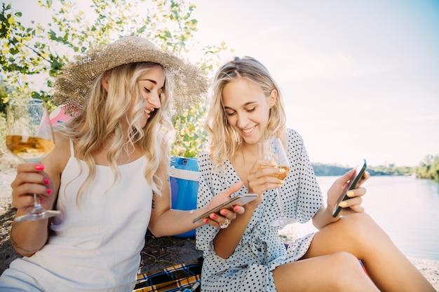 Para młodych lesbijek bawi się nad rzeką w słoneczny dzień. kobiety wspólnie spędzają czas na łonie natury. picie wina, robienie selfie. pojęcie związku, miłości, lata, weekendu, miesiąca miodowego.