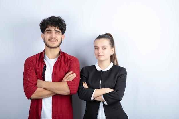 Para młodych przyjaciół stojących ramionami skrzyżowanymi na białym tle. wysokiej jakości zdjęcie