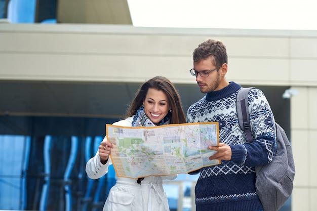 Para młodych turystów czyta mapę i szuka lokalizacji w mieście