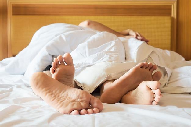 Para na białym łóżku w pokoju hotelowym skupia się na stopy