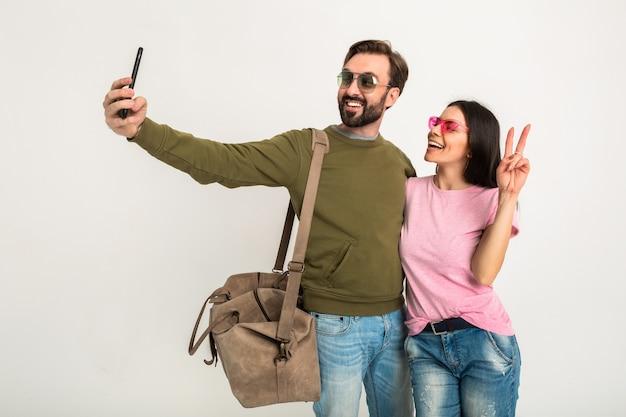 Para na białym tle, dość uśmiechnięta kobieta w różowej koszulce i mężczyzna w bluzie z torbą podróżną, w dżinsach i okularach przeciwsłonecznych, dobrze się bawią, podróżują razem robiąc śmieszne selfie zdjęcie na telefon