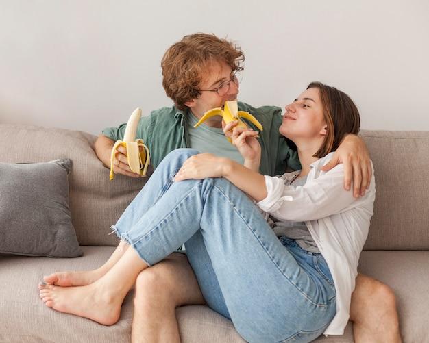 Para na kanapie, jedzenie bananów