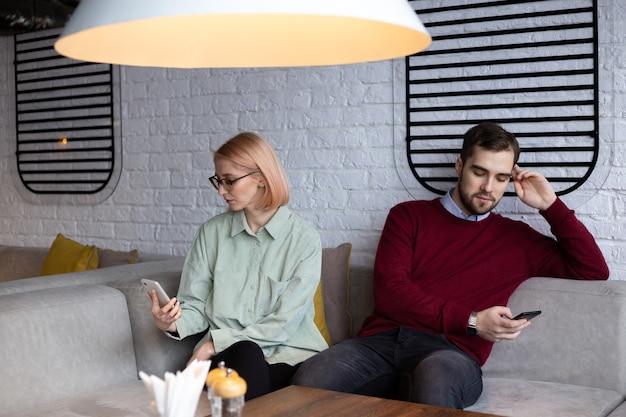 Para na nudnej randce, tkwiąca w gadżetach, wzajemnie się ignorująca