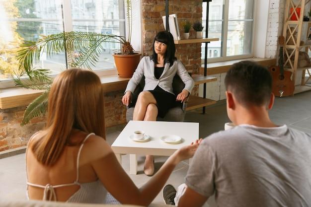Para na terapii lub poradnictwie małżeńskim. psycholog, doradca, terapeuta lub konsultant ds. relacji udzielający porad. mężczyzna i kobieta siedzą na sesji psychoterapii. rodzina, koncepcja zdrowia psychicznego.