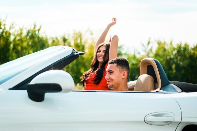 Para na wycieczce samochodowej cieszy się słońce
