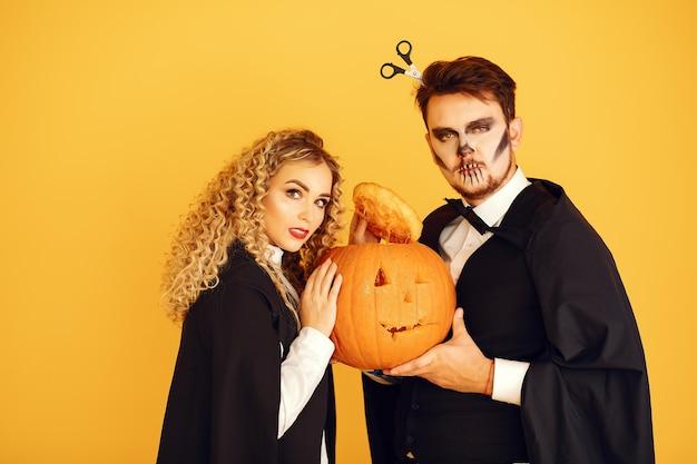 Para na żółtym tle. kobieta ubrana w czarny kostium. pani z halloweenowym makijażem.