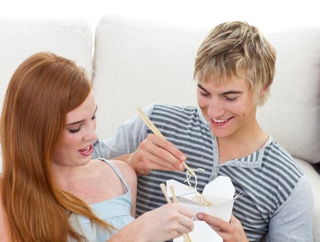 Para nastolatków jedzenia makaronu