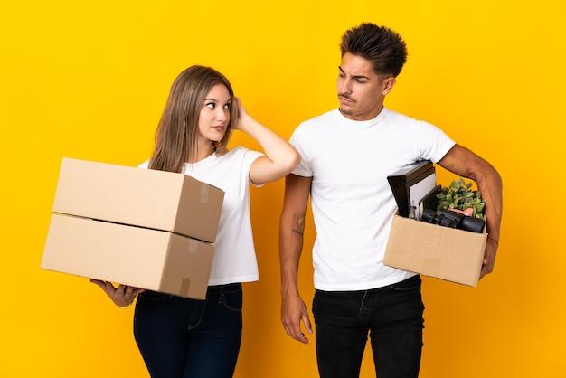 Para nastolatków porusza się w nowym domu wśród pudeł na niebiesko, mając wątpliwości podczas drapania głowy