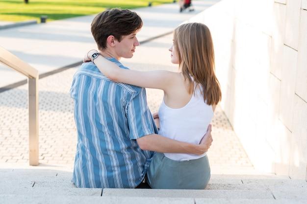 Para nastolatków trzymających się za ręce i przytulających się w parku pierwsza miłość