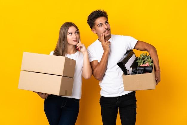 Para nastolatków w nowym domu wśród pudełek na niebiesko myśli pomysł, patrząc w górę
