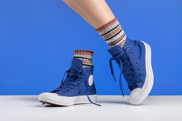 Para niebieskich sznurowanych trampek jedna kobieca noga w butach na niebieskim tle