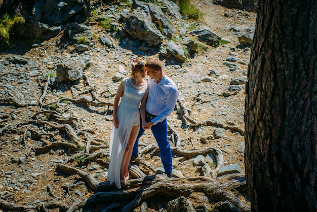 Para nowożeńców stoi w dzikiej przyrodzie i patrzy na siebie.
