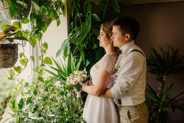 Para nowożeńców zakochana obejmuje wyglądając przez okno, będąc we wnętrzu naprzeciwko zielonych roślin.