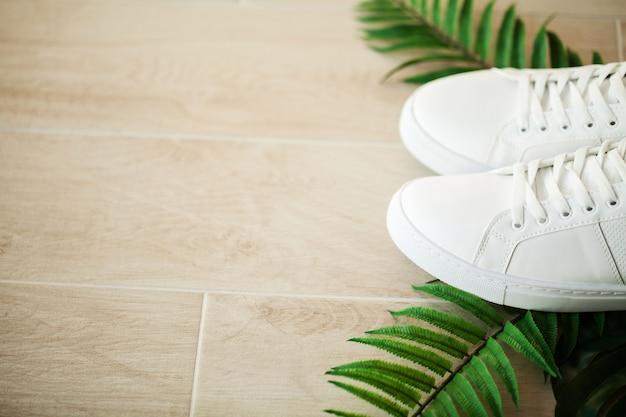 Para nowych stylowych białych tenisówek na drewnianej podłodze.