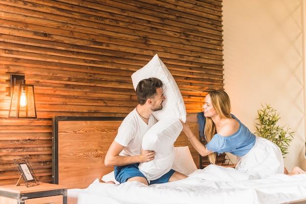Para o bitwę na poduszki na łóżku