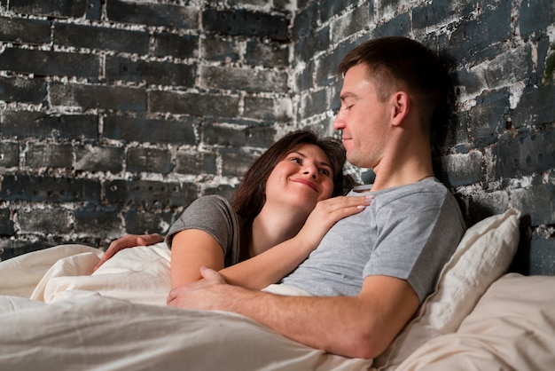 Para obejmująca w łóżku z kopii przestrzenią