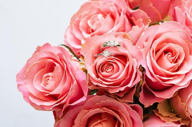 Para obrączek umieszczonych na bukiet różowych róż na walentynki.