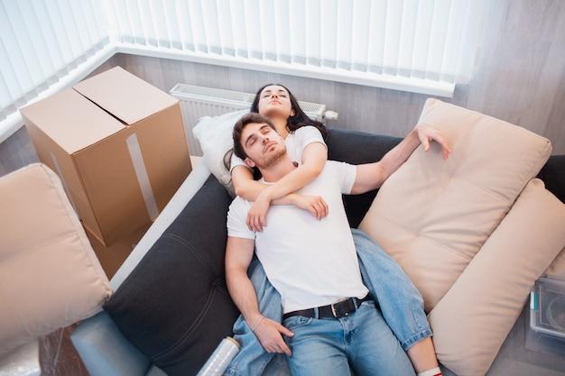 Para odpoczywa na kanapie po przeprowadzce, mężczyzna i kobieta relaksujący na kanapie właśnie wprowadzili się do mieszkania z kartonowymi pudełkami na podłodze, zadowoleni zadowoleni właściciele domów cieszący się pierwszego dnia w nowym domu, widok z góry