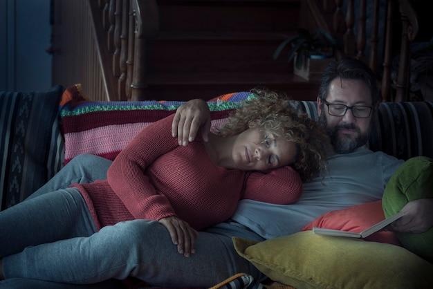 Para odpoczywa nocą w domu ze śpiącą kobietą i mężczyzną czytającym razem książkę na kanapie