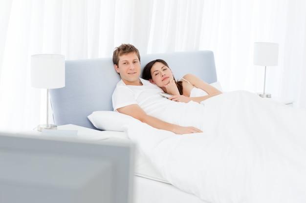 Para ogląda tv w ich łóżku