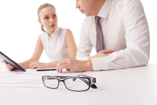 Para okularów na stole biurowym i dwóch biznesmenów nad dyskusją w tle.