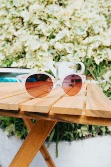 Para okularów przeciwsłonecznych nad drewnianym stołem, koncepcja lato i wakacje