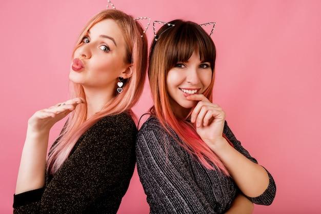 Para oszałamiających kobiet w stylowych sukienkach i pozujących kocich uszach