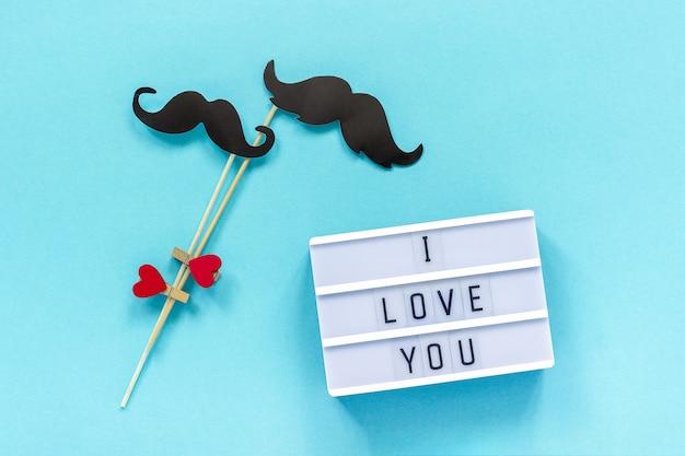 Para papieru wąsy rekwizyty i lekkie pudełko z tekstem kocham cię na niebieskim tle.