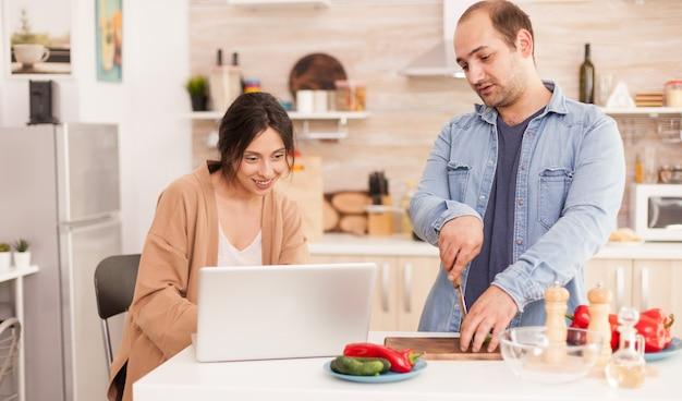 Para patrząc na przepis online na zdrowy posiłek w kuchni. mężczyzna pomaga kobiecie przygotować zdrowy organiczny obiad, wspólne gotowanie. romantyczny, wesoły związek miłosny