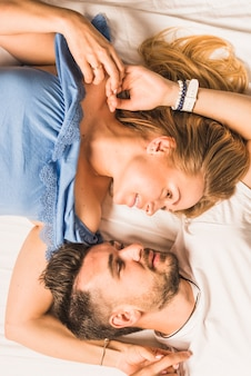 Para patrząc na siebie, leżąc na łóżku