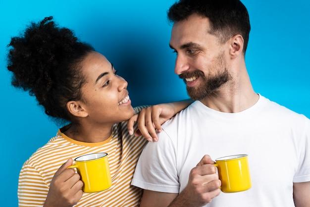 Para patrząc na siebie trzymając kubki