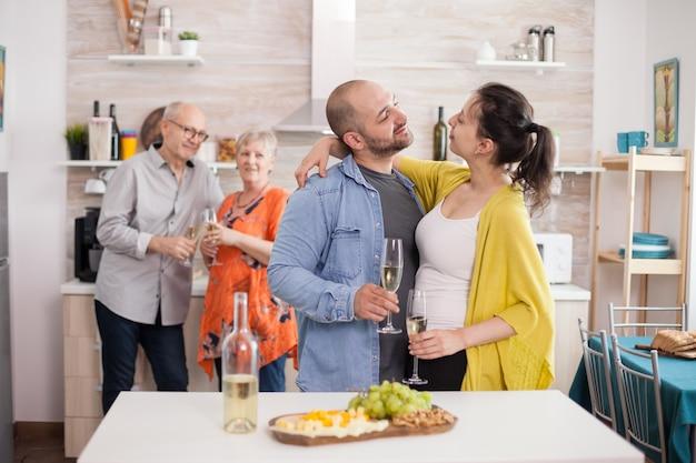 Para patrząc na siebie w kuchni podczas rodzinnego brunchu. mężczyzna trzyma kieliszek wina. przystawka z różnymi serami.