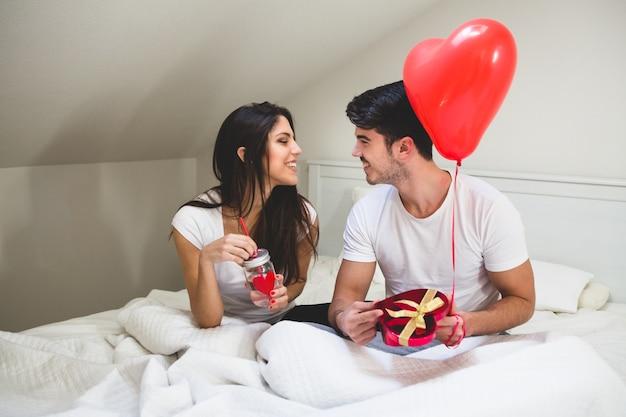 Para patrząc sobie w oczy, gdy pan młody trzyma prezent i balon