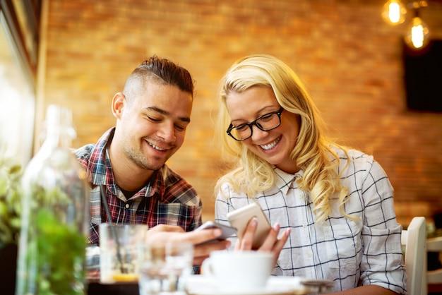 Para patrzeje mądrze telefony przy kawiarnia barem.