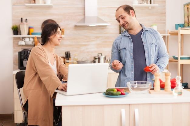 Para patrzy na przepis na sałatkę ekologiczną na laptopie w kuchni. mężczyzna pomaga kobiecie przygotować zdrowy organiczny obiad, wspólne gotowanie. romantyczny, wesoły związek miłosny