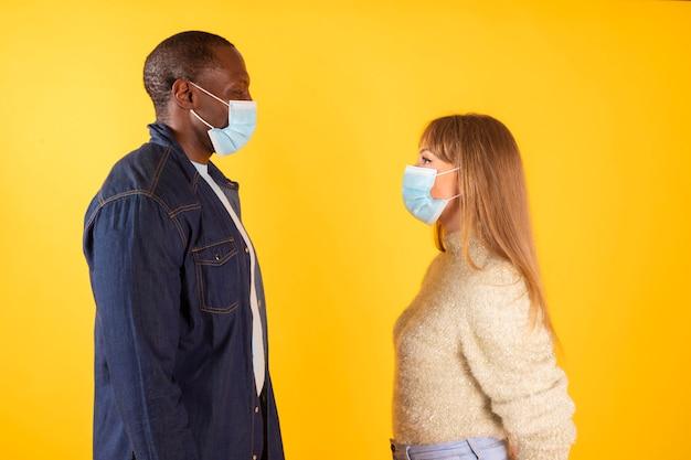 Para patrzy na siebie z maską medyczną, widok profilu międzyrasowego,