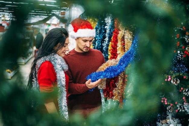 Para patrzy na świąteczne dekoracje w supermarkecie