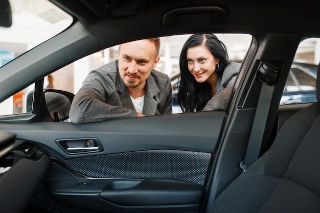 Para patrzy na wnętrze nowego samochodu w salonie.