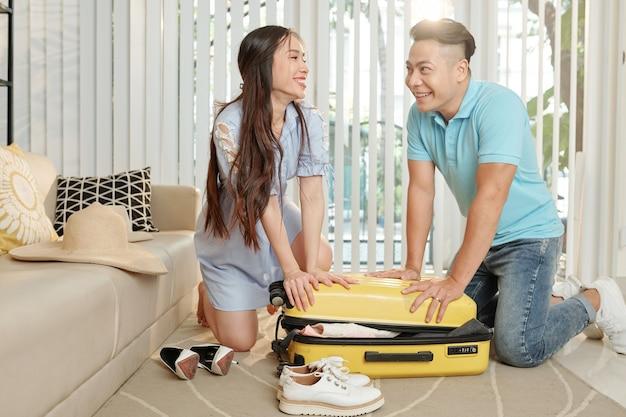 Para pchająca walizkę