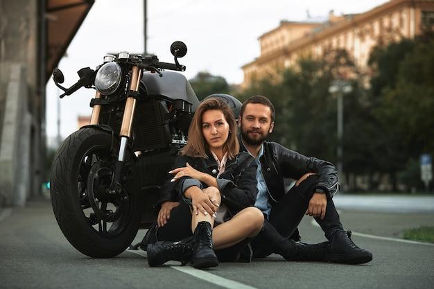 Para pięknych kochanków siedzi przytulając się obok motocykla na drodze w mieście