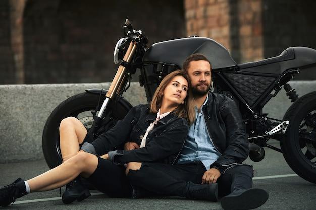 Para pięknych kochanków siedzi przytulona przy motocyklu na drodze w mieście