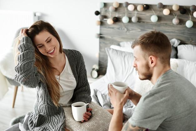 Para pijąca poranną kawę w sypialni