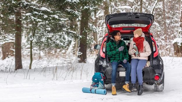 Para pije herbatę siedząc na bagażniku samochodu