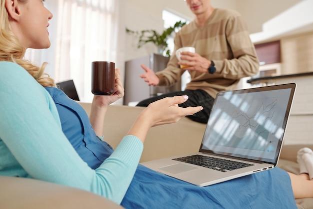 Para pije kawę i omawia wykres giełdowy oraz możliwości inwestowania