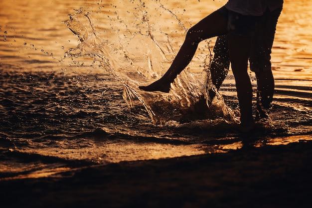 Para plusk ich stopy w wodzie o zachodzie słońca