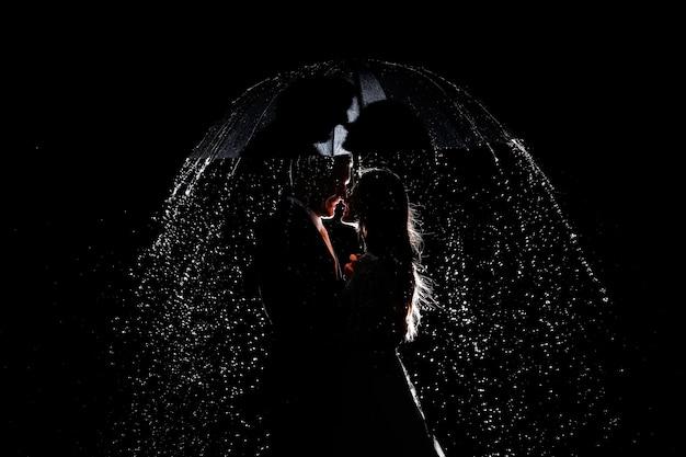 Para pod parasolem w nocy w deszczu