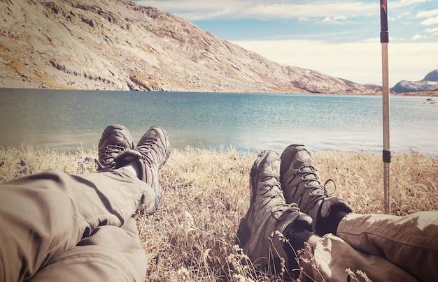 Para podróżnik relaks po wędrówkach w pobliżu jeziora w górach.
