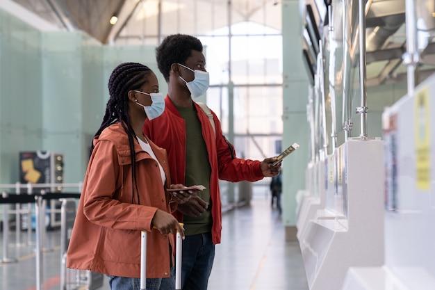 Para podróżnych w masce przy stanowisku odprawy na lotnisku przed lotem podczas epidemii koronawirusa