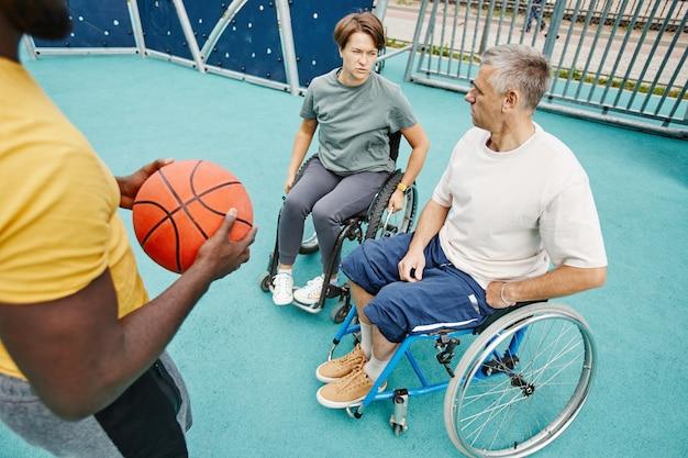 Para porażona paraplegią rozmawia z trenerem na zewnątrz