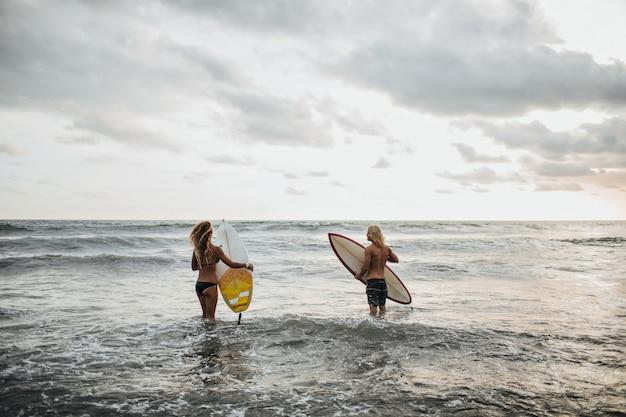 Para pozuje na plaży i surfuje